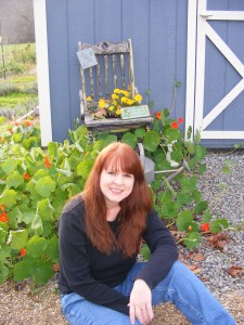 Kathy in front of greenhouse